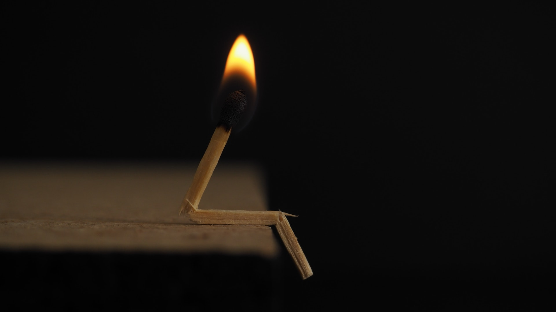 A match broken into a sitting position with its sulfer head burning. Kind of looks like a piano player that has warmed up before starting to play.